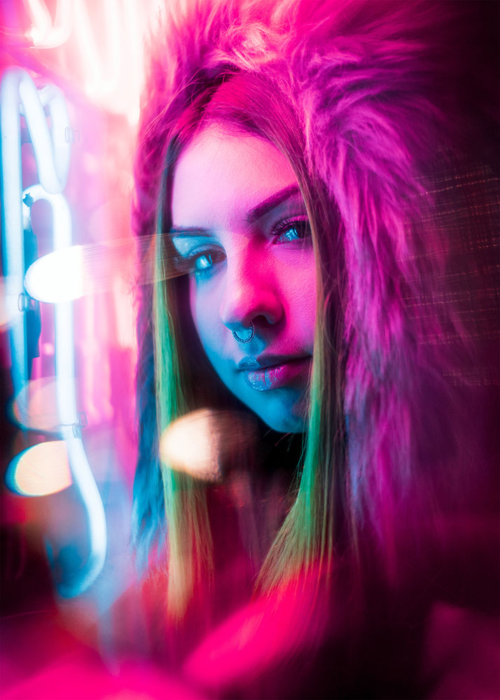 JT portrait of a woman looking at the camera, lit by pink neon