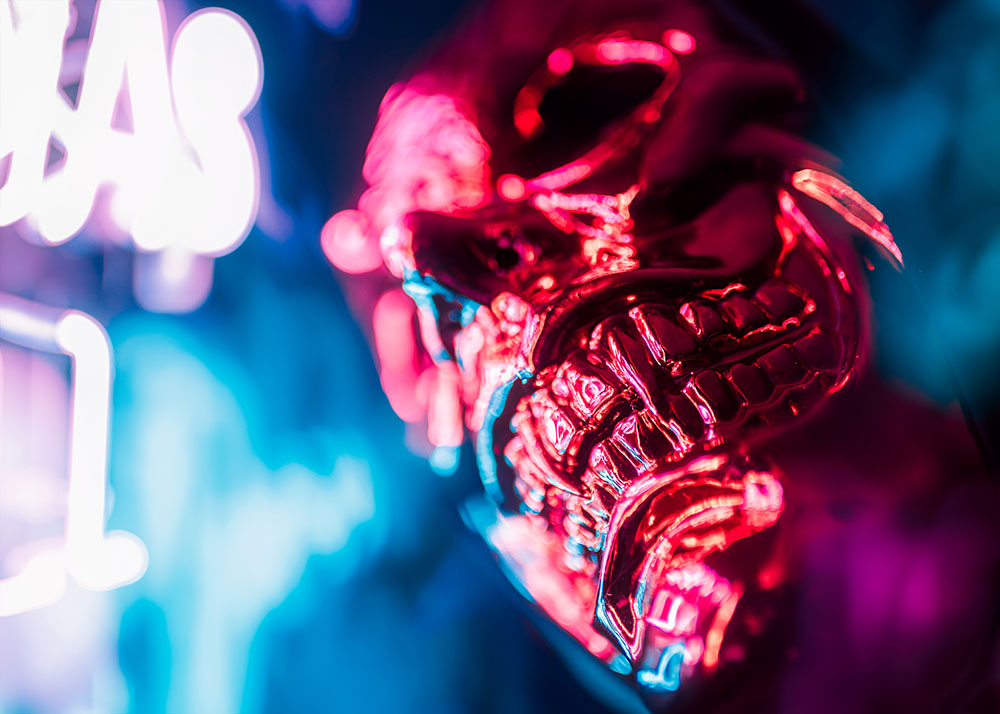 JT photo of a metallic looking skull, lit with neon lights