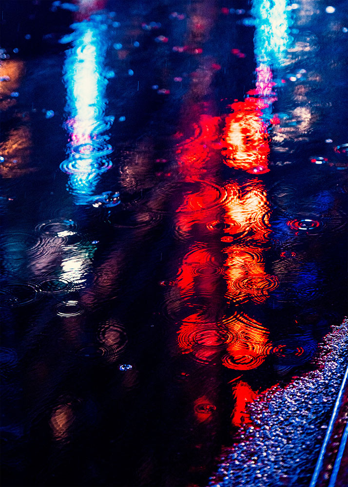 JT photo of the reflection of lights in a puddle on a wet street
